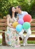 Lyckliga romantiska par sitter på bänk i stad parkerar och kysser, sommarsäsongen, den vuxna folkmannen och kvinnan Royaltyfri Bild