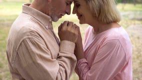 Lyckliga romantiska par som rymmer händer som ler förälskade morföräldrar, closeness royaltyfria bilder