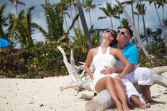 Lyckliga romantiska par som tycker om solnedgång på stranden Royaltyfria Foton