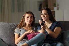 Lyckliga rumskamrater som wathing tv i natten royaltyfria bilder