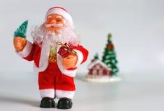 Lyckliga Santa Claus Doll på jultid färgrik bakgrundsbokeh Arkivfoto