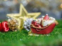 Lyckliga Santa Claus med gåvaasken på snösläden bakgrunden är juldekoren Santa Claus och juldekor på grönt gräs Arkivbild