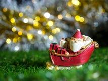 Lyckliga Santa Claus med gåvaasken på snösläden bakgrunden är juldekoren Santa Claus och juldekor på grönt gräs Arkivfoto