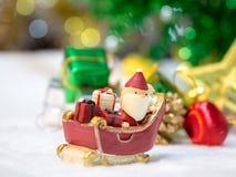 Lyckliga Santa Claus med gåvaasken på snösläden bakgrunden är juldekoren Santa Claus och juldekor på snön Arkivbilder