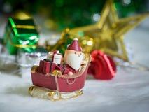 Lyckliga Santa Claus med gåvaasken på snösläden bakgrunden är juldekoren Santa Claus och juldekor på snön Arkivfoto