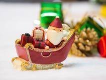 Lyckliga Santa Claus med gåvaasken på snösläden bakgrunden är juldekoren Santa Claus och juldekor på snön Royaltyfria Foton