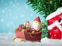 Lyckliga Santa Claus med gåvaasken på snösläden som går att inhysa nära hus ha snögubben och julgranen claus santa Arkivfoto