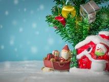 Lyckliga Santa Claus med gåvaasken på snösläden som går att inhysa nära hus ha snögubben och julgranen claus santa Royaltyfri Fotografi
