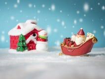 Lyckliga Santa Claus med gåvaasken på snösläden som går att snöa huset nära snöhus ha snögubben och julgranen Arkivbild