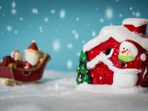 Lyckliga Santa Claus med gåvaasken på snösläden som går att snöa huset nära snöhus ha snögubben och julgranen Arkivfoto