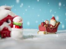 Lyckliga Santa Claus med gåvaasken på snösläden som går att snöa huset nära snöhus ha snögubben och julgranen Royaltyfri Foto