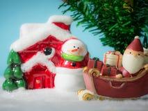 Lyckliga Santa Claus med gåvaasken på snösläden som går att snöa huset nära snöhus ha snögubben och julgranen Fotografering för Bildbyråer