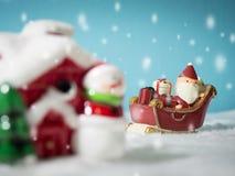 Lyckliga Santa Claus med gåvaasken på snösläden som går att snöa huset nära snöhus ha snögubben och julgranen Royaltyfria Foton