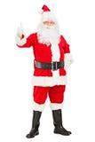 Lyckliga Santa Claus som plattforer upp och ger en tum Royaltyfria Bilder