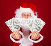 Lyckliga santa hållande dollar Fotografering för Bildbyråer