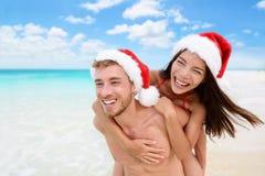 Lyckliga santa hattpar på jul semestrar stranden Arkivfoton