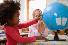 Lyckliga schoolgirls som ser ett jordklot Royaltyfria Bilder
