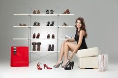 lyckliga seende skor som sitter försökande kvinnabarn Arkivfoto