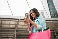 Lyckliga shopaholic flickaräkningspengar för att shoppa Royaltyfria Bilder