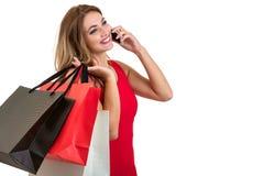 Lyckliga shoppingpåsar och mobiltelefon för ung kvinna hållande över vit bakgrund Arkivbild
