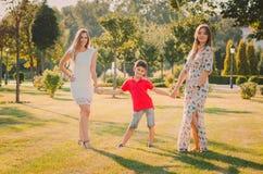 Lyckliga sju har gyckel på gräsmattan De rymmer händer lycklig begreppsfamilj royaltyfri foto