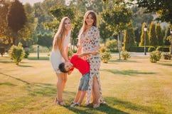 Lyckliga sju har gyckel på gräsmattan De rymmer händer lycklig begreppsfamilj fotografering för bildbyråer