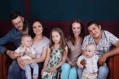 Lyckliga sju personer - fyra vuxna människor och tre barn sitter Royaltyfri Foto