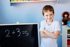 Lyckliga sju år gammal pojke i klassrum Arkivbilder