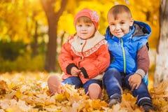 Lyckliga skämtsamma barn i hösten parkerar Arkivbild