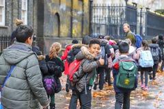 Lyckliga skolapojkar och flickor i London royaltyfri bild