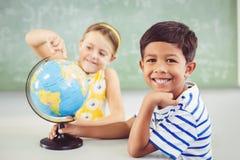 Lyckliga skolaungar med jordklotet i klassrum arkivfoton
