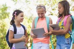 Lyckliga skolaungar som använder den digitala minnestavlan royaltyfria bilder