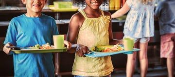 Lyckliga skolbarn som rymmer matmagasinet i kantin arkivbilder