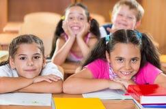 Lyckliga skolbarn under kurs i klassrum arkivfoton