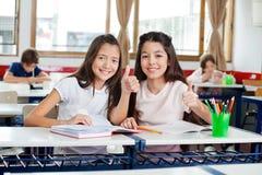 Lyckliga skolflickor som gör en gest upp tummar på skrivbordet Arkivbild