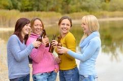 Lyckliga skratta kvinnor som rostar med öl Arkivfoton