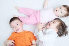 Lyckliga skratta ungar, tre olika åldrar för barn som ligger, ståenden av pojken, liten flicka och behandla som ett barn flickan Arkivbild