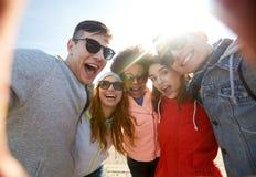 Lyckliga skratta vänner som tar selfie Arkivfoton