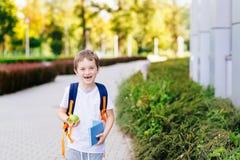 Lyckliga små 7 år gammal pojke på hans första dag på skolan Arkivbild