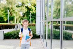 Lyckliga små 7 år gammal pojke på hans första dag på skolan Fotografering för Bildbyråer