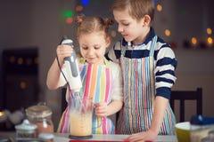 Lyckliga små barn som förbereder julkakor arkivfoto