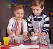 Lyckliga små barn som förbereder julkakor arkivbild