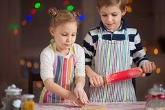 Lyckliga små barn som förbereder julkakor arkivbilder