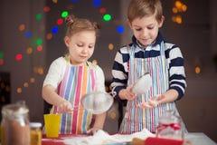 Lyckliga små barn som förbereder julkakor royaltyfria foton