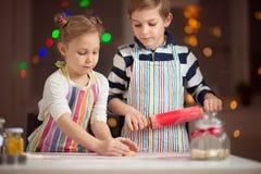 Lyckliga små barn som förbereder julkakor royaltyfria bilder