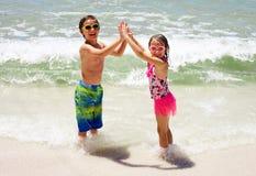 Lyckliga små barn som rymmer händer på stranden Arkivbilder