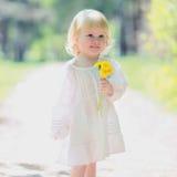 Lyckliga små behandla som ett barn flickan med den gula maskrosen Royaltyfri Bild