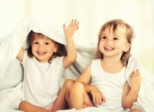 Lyckliga små flickor kopplar samman systern i säng under filten som den har Royaltyfri Bild