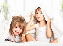 Lyckliga små flickor kopplar samman systern i säng under filten som den har Fotografering för Bildbyråer