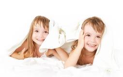 Lyckliga små flickor kopplar samman systern i säng under filten som har gyckel Arkivfoto